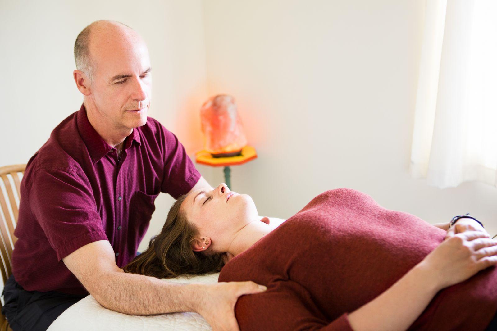 Aumkara Newhouse applying Meridian Charging Therapy - Jin shin Jyutsu to base of skull and shoulder